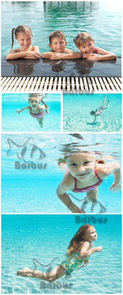 Children swim in the pool / Дети плавают в бассейне - Photo stock