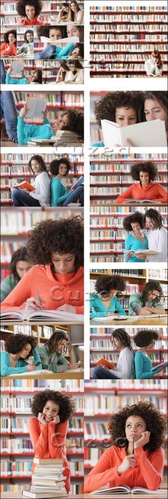 Студенты с книгами в библиотеке/ Students in the library - Stock photo
